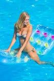 Una muchacha es relajante en una piscina Fotos de archivo libres de regalías