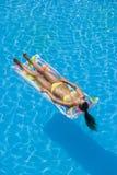 Una muchacha es relajante en una piscina Imagen de archivo libre de regalías