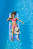 Una muchacha es relajante en una piscina Imagen de archivo