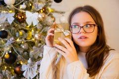 Una muchacha escucha una caja con un regalo Él intenta conjeturar qué GIF Foto de archivo libre de regalías