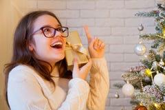 Una muchacha escucha una caja con un regalo Él intenta conjeturar qué GIF Fotografía de archivo libre de regalías