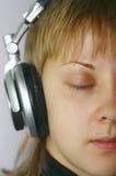Una muchacha escucha música Foto de archivo libre de regalías