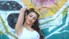 Una muchacha está bailando contra un fondo colorido de la pared