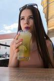 Una muchacha está bebiendo un mojito tropical en un café del verano Una muchacha con vidrios, un vestido rosado y los labios rojo Foto de archivo