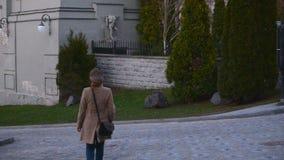Una muchacha está caminando a lo largo de la calle de la ciudad de Kiev Contra la perspectiva de las estructuras arquitectónicas metrajes