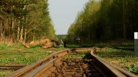 Una muchacha está caminando a lo largo de las pistas ferroviarias almacen de video