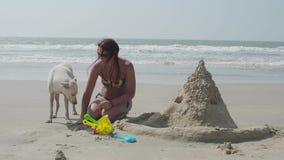 Una muchacha está construyendo un castillo de la arena en la costa que abraza un perro blanco 4K almacen de metraje de vídeo