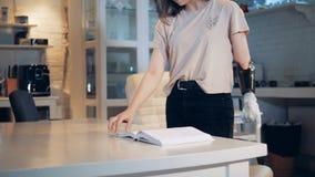 Una muchacha está enrollando las páginas del libro con un brazo prostético Robótico real humano-como el brazo