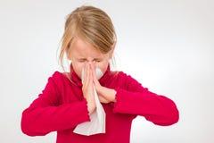 Una muchacha está estornudando en un pañuelo blanco Ella es 7 años y lleva un jersey rojo Imagen de archivo