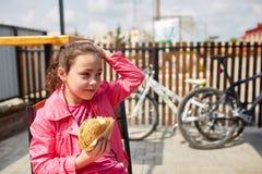 Una muchacha está gozando de una hamburguesa del queso en el café del aire abierto delante del estacionamiento de la bici Imagenes de archivo