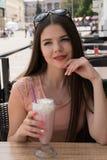Una muchacha está gozando de un batido de leche en un café del verano Día de verano asoleado en la ciudad Fotos de archivo