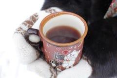 Una muchacha está guardando la taza con té negro caliente imagenes de archivo