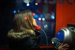 Una muchacha está hablando en un teléfono público en la noche en la calle fotos de archivo