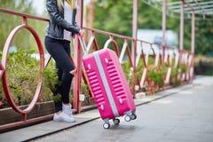 Una muchacha está haciendo una pausa la verja con una maleta rosada Imagen de archivo