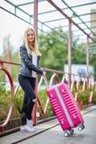 Una muchacha está haciendo una pausa la verja con una maleta rosada Fotografía de archivo libre de regalías