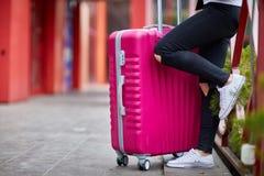 Una muchacha está haciendo una pausa la verja con una maleta rosada Fotos de archivo libres de regalías