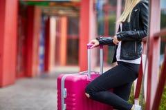 Una muchacha está haciendo una pausa la verja con una maleta rosada Imágenes de archivo libres de regalías