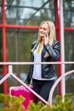 Una muchacha está haciendo una pausa la verja con una maleta rosada Imagen de archivo libre de regalías