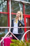 Una muchacha está haciendo una pausa la verja con una maleta rosada Foto de archivo