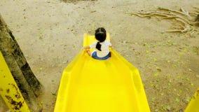 Una muchacha está jugando la diapositiva amarilla solamente en el parque por la tarde después de lluvia con felicidad y alegre almacen de video