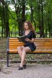 Una muchacha está leyendo en el parque Fotos de archivo