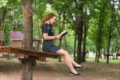 Una muchacha está leyendo en el parque Imágenes de archivo libres de regalías