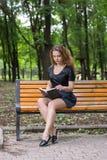 Una muchacha está leyendo en el parque Fotografía de archivo