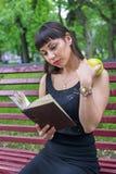 Una muchacha está leyendo un libro Imagen de archivo