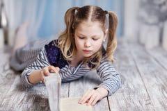 Una muchacha está leyendo un libro que miente en el piso Imagenes de archivo