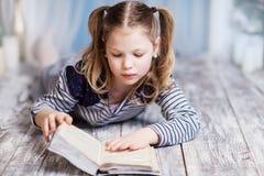 Una muchacha está leyendo un libro que miente en el piso Fotos de archivo libres de regalías