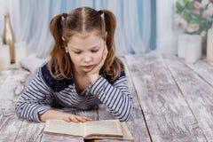 Una muchacha está leyendo un libro que miente en el piso Imagen de archivo