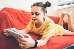 Una muchacha está mintiendo en un sofá rojo en el balcón con una tableta imágenes de archivo libres de regalías