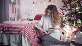 Una muchacha está mirando un álbum de foto cerca de un árbol de navidad Ella es acercada por un individuo que se caiga sin éxito  metrajes