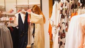 Una muchacha está mirando un vestido del verano en una tienda de ropa del ` s de las mujeres Foto de archivo libre de regalías