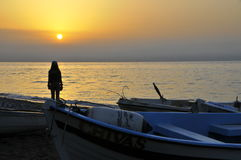 Una muchacha está mirando una salida del sol hermosa en la playa por la mañana imagen de archivo