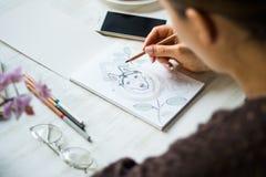 Una muchacha está pintando con los lápices fornido en una hoja blanca en un café en un fondo de madera blanco de la luz de la tab fotos de archivo