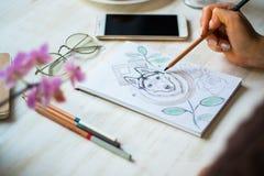 Una muchacha está pintando con los lápices fornido en una hoja blanca en un café en un fondo de madera blanco de la luz de la tab imagen de archivo