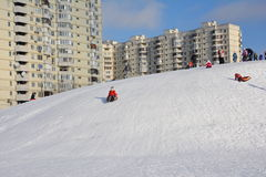 Una muchacha está resbalando abajo de una colina de la nieve en el tubo de la nieve feliz Fotos de archivo