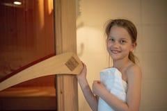 Una muchacha está sonriendo y abre la puerta de la sauna finlandesa Imágenes de archivo libres de regalías