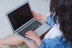 Una muchacha está sosteniendo un ordenador portátil en su revestimiento que se sienta por la cama en un fondo blanco Imagenes de archivo