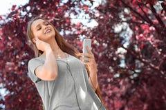 Una muchacha fantástica alegre con un teléfono en un fondo colorido Una muchacha bonita que escucha una música alegre Fotos de archivo