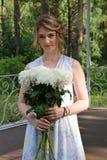 Una muchacha feliz con las flores se está colocando en un cenador del bosque Fotos de archivo libres de regalías