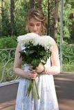 Una muchacha feliz con las flores se está colocando en un cenador del bosque Imagenes de archivo