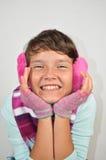 Una muchacha feliz con los manguitos del oído y los guantes cortados Fotos de archivo