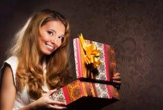 Una muchacha feliz del teenge que abre un regalo de Navidad Fotos de archivo