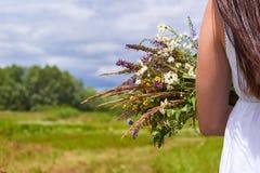 Una muchacha feliz en el vestido blanco que sostiene un ramo de wildflowers en sus manos en el campo verde Concepto de la natural Fotografía de archivo libre de regalías