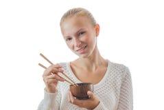 Una muchacha feliz joven con el cuenco y los palillos fotos de archivo libres de regalías