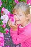 Una muchacha feliz que huele rosas rosadas. Foto de archivo