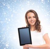 Una muchacha feliz que sostiene una tableta en un fondo nevoso Foto de archivo libre de regalías