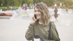 Una muchacha feliz sonriente de los jóvenes está caminando en el parque que tiene una llamada Foto de archivo libre de regalías